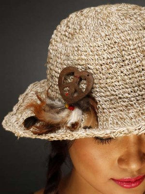 A crochet hemp hat with flower attachment.